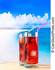 two glasses of red cocktail with blur beach and sky on...