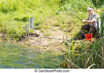 Senior man sitting fishing at the edge of a lake on a grassy...