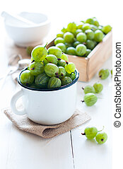 Fresh ripe green gooseberry in an enamel mug and a wooden...
