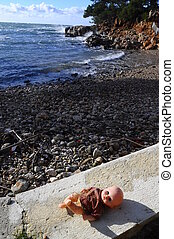 Abandoned baby doll on beach - Abandoned baby doll on pebble...