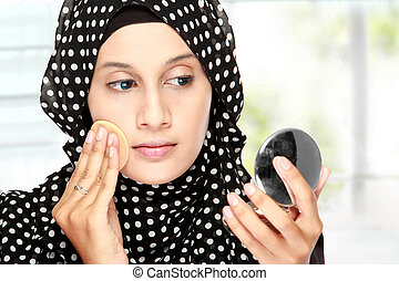 woman with cotton pad applying face powder - beautiful young...