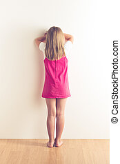 portrait of sad little girl standing near wall. studio shot
