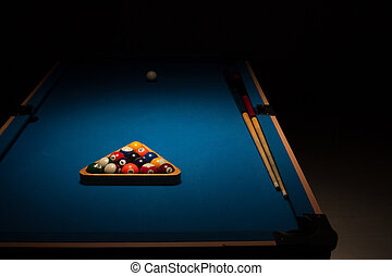 Pool balls and cues on a blue baize table - Pool balls...