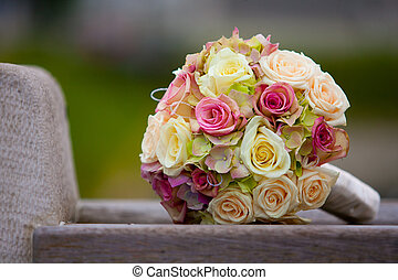 Wedding bouquet - A bouquet of roses placed on a bench in a...