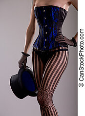 Sexy magician girl in corset and lingerie holding top hat,...