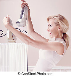 Smiling woman looking at shoes - Smiling beautiful blonde...