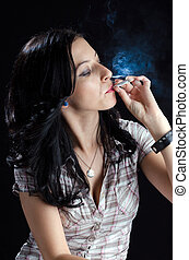 Woman Smoking a Cannabis Joint - Attractive woman smoking a...