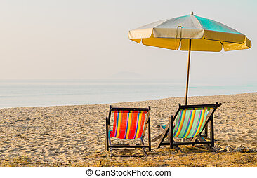 Vacation concept: Pair of beach loungers on the deserted coast i