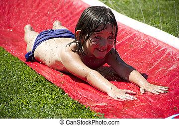 summertime - Gilr slides across a slip and slide on the...