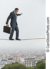 businessman walking across a tightrope above a city