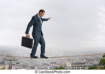 businessman walking tightrope above city - businessman...