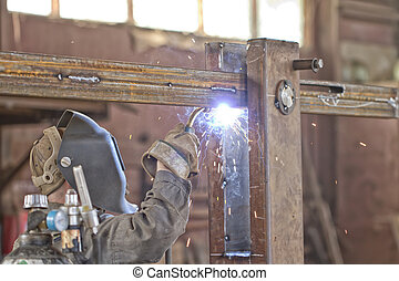 Welder brews metal structure in the shop. Semiautomatic...