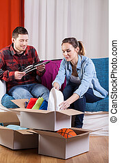Couple moving house - Happy couple packing things because of...
