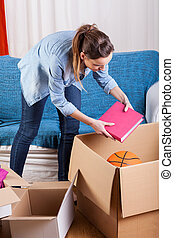 Woman moving house - Young woman moving house and packing...