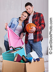 Young couple moving house - Young happy couple packing...