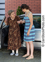 Elderly lady after driving in front of house