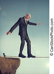 senior man walking a tightrope - senior man walking on a...