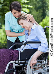 Nurse hugging woman on a wheelchair in a garden