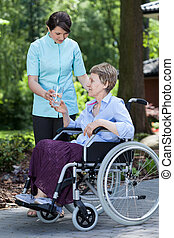 Disabled woman with glass of water in a garden