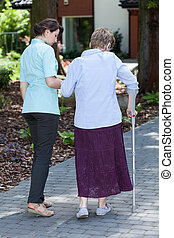 Woman on crutches in a garden - Woman walking on crutches in...