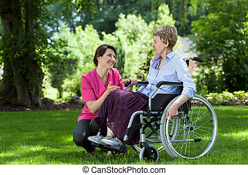 Woman on wheelchair relaxing in garden with nurse