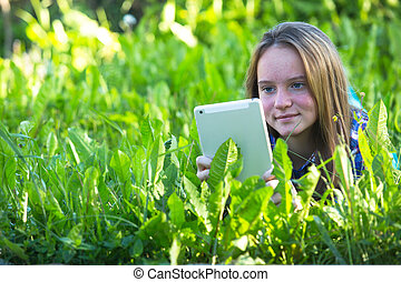 Nice young girl with a tablet PC lying in the grass.