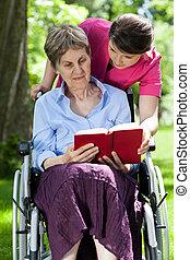 Woman on wheelchair reading book in a garden