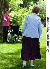 Disabled woman during free time with nurse in garden