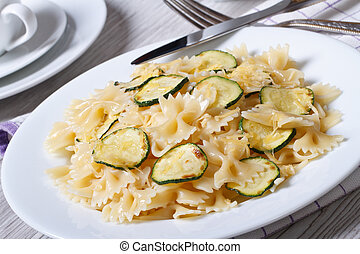 Farfalle pasta with zucchini slices closeup with a fork -...
