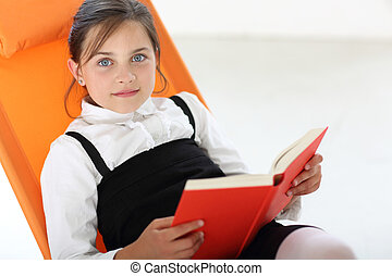 smiling girl - Joyful girl reading a book sitting on the...
