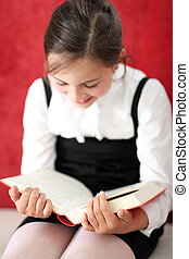 Girl reading a book - Joyful girl reading a book sitting on...