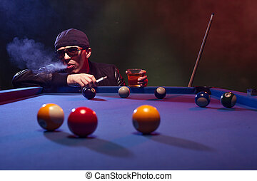 Man playing pool in a club smoking e-cigarette - Man in...