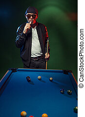 Trendy pool player in a leather jacket and cap - Trendy pool...