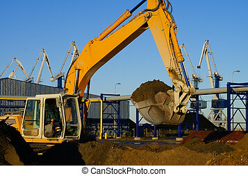 Hydraulic excavator at work Shovel bucket and cranes against...