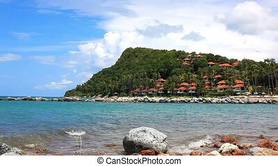 Beautiful Andaman Sea and Blue Sky. landscape on island with houses, trees in mountain, waves beating against rocks. Video