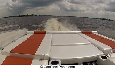 Rear area of pontoon navigating at full speed on calm lake