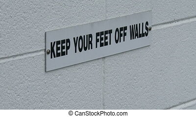 Keep your feet off walls sign on white wall