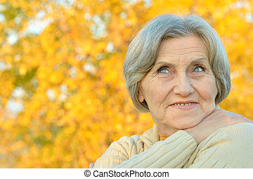 Portrait of smiling senior woman in autumn park