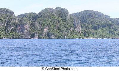 Boat floats ocean island - Boat floats on the azure ocean in...