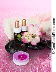 Candle, flower, stones with water drops, on the pink