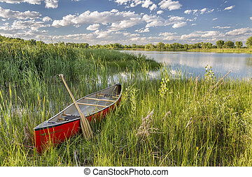 red canoe on lake shore - red canoe with a wooden paddle on...