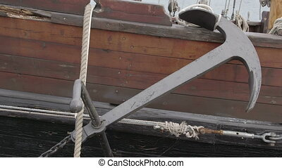 Black anchor from a brown boat on dock in harbour FS700...
