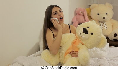 Wicked girl talking on the phone. Teddy toy