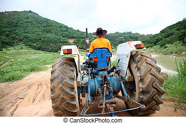 Farmer driving tractor - Farmer driving tractor in the rural...