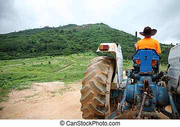 Farmer driving tractor. - Farmer driving tractor in the...