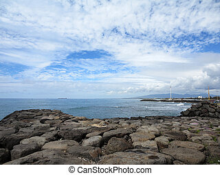 Rock Shore of Kakaako with ocean and westside of Oahu...