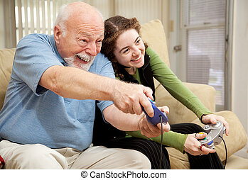 Grandpa and Teen Play Video Games - Grandfather enjoys...