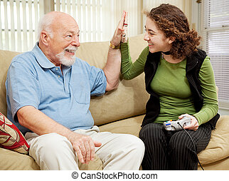 High Five for Grandpa - Teen girl playing video games,...
