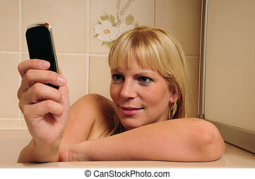 happy blond woman taking a bath and using cellphone