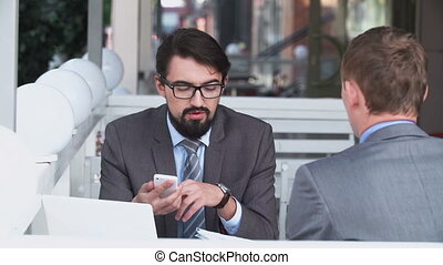 Business Lunch - Two businessmen in street restaurant...